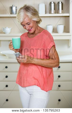 Senior woman using mobile phone while having coffee in kitchen at home