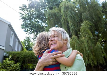 Grandfather hugging grandson at back yard