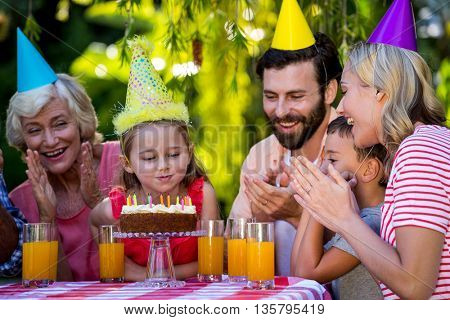 Family celebrating birthday of girl at yard