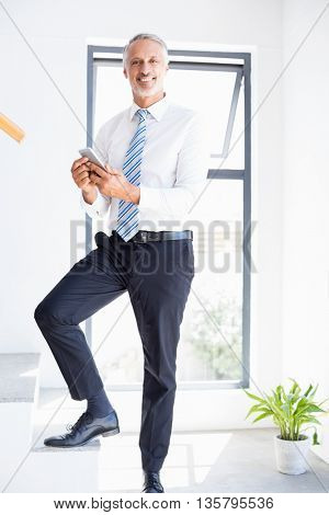 Portrait of businessman holding mobile phone in the office