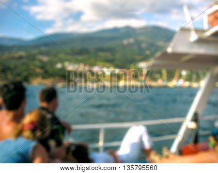 Young people on sea walk admire the mountainous coast. Travel theme blur background and white bokeh.