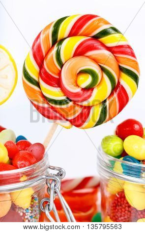 Lollipops candy and chewing gum in the jar of glass closeup on a white background