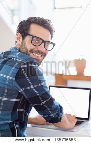 Portrait of happy young man using laptop at home