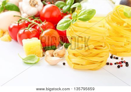 Fettuccine with ingredients for cooking pasta on a white background closeup