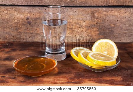 water with the lemon and honey on table