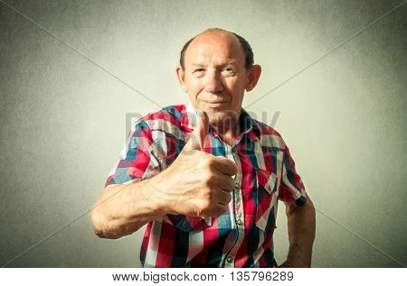 portrait of the funny senior man doing thumbs up