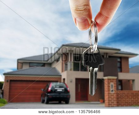 key in hand with real estate on background
