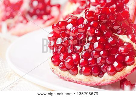 Closeup sliced pomegranate on a white plate