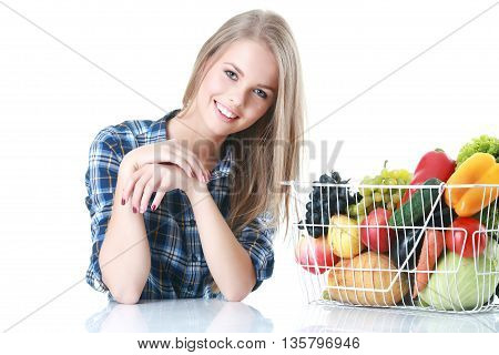 Isolated young woman holding basket of vegetables on light backgraund