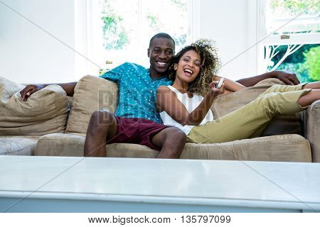 Young couple watching television while relaxing on the sofa