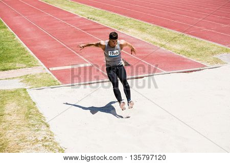 Athlete performing a long jump during a competition