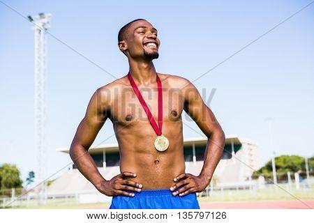Athlete posing with gold medals around his neck in stadium