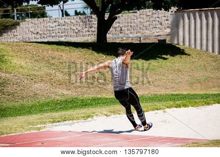 Rear view of athlete performing a long jump during a competition