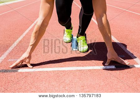 Athlete on a starting block about to run on running track