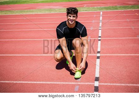 Portrait of male athlete tying her shoe laces on running track on a sunny day
