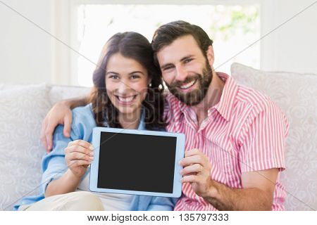 Portrait of couple showing digital tablet in living room