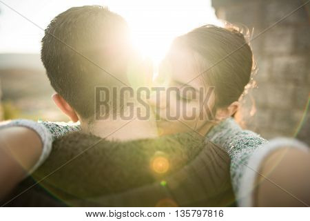 Young couple in love hugging in the nature enjoying and looking in the sunset