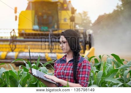Farmer Girl On Field With Combine Harvester
