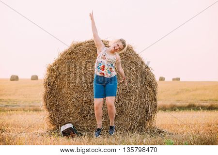 Beautiful Plus Size Young Woman Girl Jumping Near Haystack With His Hand Up And Smiling. Sunset Of The Day In Summer Field Meadow