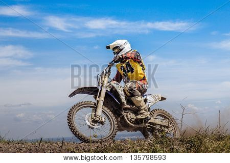 racer on a motorcycle on top of a mountain on background of blue sky