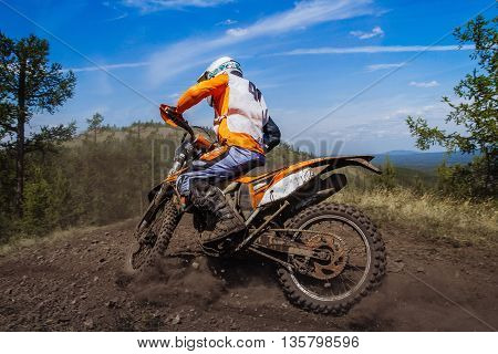 rider rides on mountain dirt and stones from under wheels