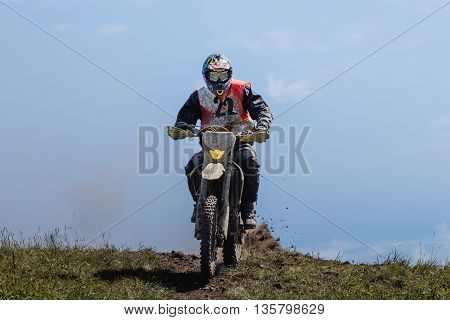 athlete rider on top of mountain from under rear wheel spray of dust and stones