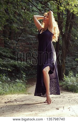 Beautiful relaxed woman in sundress in sunny summer forest