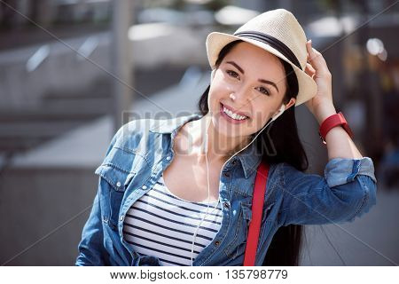 Share your emotions. Positive delighted smiling young woman touching her hat and listening to music while having a walk