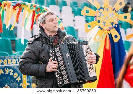 Gomel, Belarus - March 12, 2016: Unknown man plays the accordion folk Belarusian music at Celebration of Maslenitsa Shrovetide holiday in Gomel, Belarus.