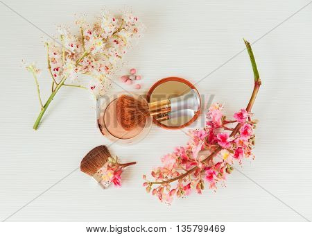 There White and Pink  Branches of Chestnut Tree,Bronze Powder with Mirror and Make Up Brush are on White Table,Top View