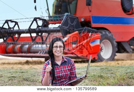 Farmer Girl With Laptop And Combine Harvester