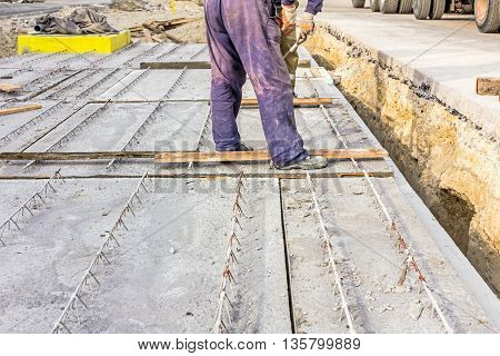 Workers are set up concrete slab to assembly underground edifice.