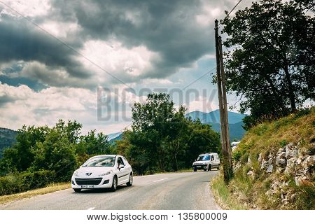 Verdon, France - June 29, 2015: White colour Peugeot 308 3-door car and Peugeot Partner car on background of French mountain nature landscape