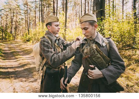 Teryuha, Belarus - October 3, 2015: Two unidentified re-enactors dressed as World War II Russian Soviet Soldiers In Camouflage In Forest
