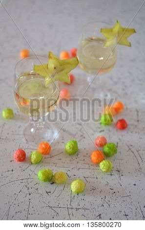 Wineglasses of champagne decorated with fruit and snacks
