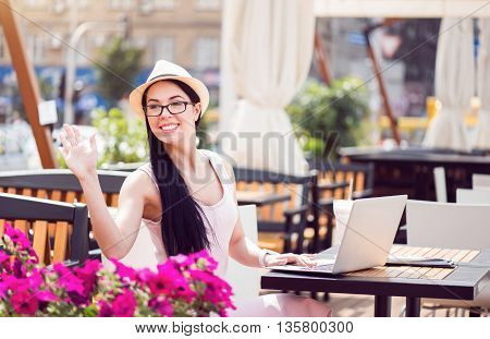 Hey. Positive smiling beautiful young woman calling someone and sitting at the table while resting on the terrace