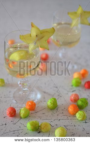 Two glasses of champagne decorated with carambola and snacks