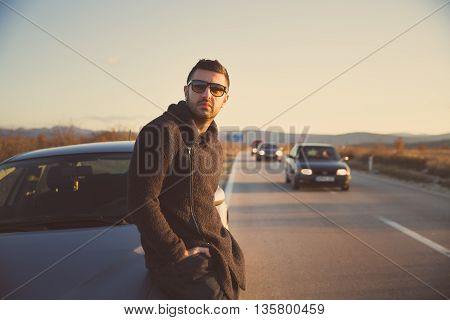 Road trip break after long drive.Young stylish man enjoys sunset.Young man fascinated by illuminated nature, escaping from everyday job problems.Road trip waiting for someone.
