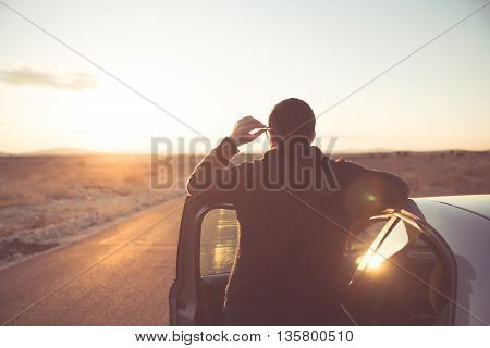 Road trip break after long drive.Young stylish man enjoys sunset.Young man fascinated by illuminated nature, escaping from everyday job problems.Pollution getaway to mountain hill for some clean air
