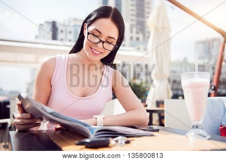 Have a nice rest. Pleasant delighted smiling young woman sitting at the table and reading magazine while resting in the cafe