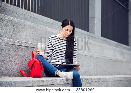 My average day. Pleasant beautiful woman sitting on the footsteps and drinking coffee while using tablet