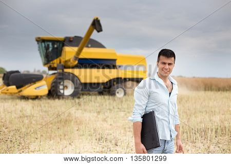 Young businessman standing with laptop on field combine harvester in background