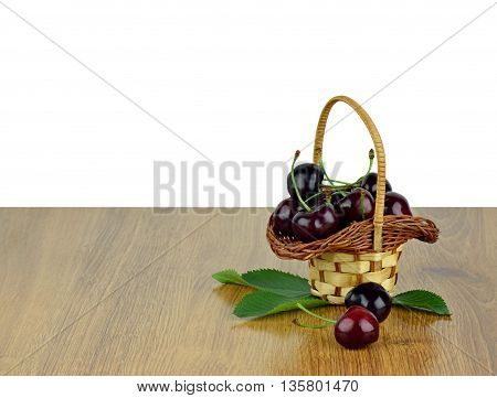 Basket of juicy sweet cherries with leaves on a wooden background. / isolated on white background /. Summer. Artisan Food. Diet. Natural Vitamins.