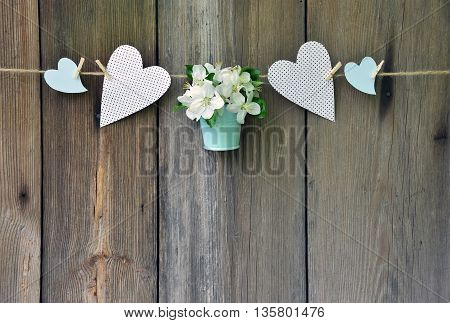 Blooming apple tree in a blue basket and colorful hearts on old wooden background. Wedding decoration in a rustic style. Rustic style. Celebration. Love. Greeting. Spring.