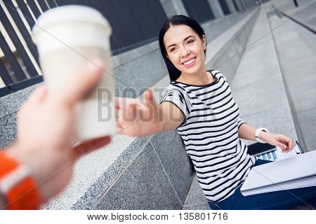 Give it to me. Positive delighted beautiful woman sitting on the footsteps and getting coffee while smiling
