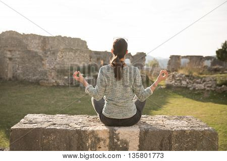 Yoga and meditation concept.Woman meditating in sitting yoga position outdoors.Woman alone practicing mindfulness meditation to clear her mind.Zen,meditation,peace concept