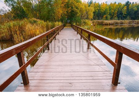 Beautiful old wooden pier, bridge for fishing and autumn forest in background. Picturesque natural landscape. Vacation concept.