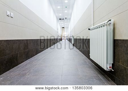 White radiator in long narrow corridor with tilled wall and floor.