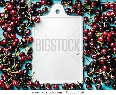 Sweet cherries in blue wooden tray with white ceramic board in center, top view, copy space