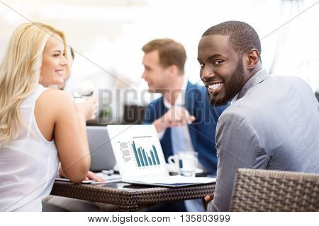 Glad to work with them. Pleasant cheerful man sitting at the table with his colleagues and smiling while being involved in work